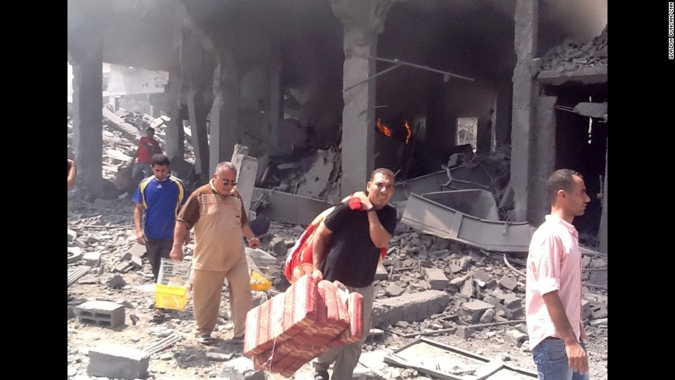 Residents return to the neighborhood in Gaza and sift through the rubble for their belongings.
