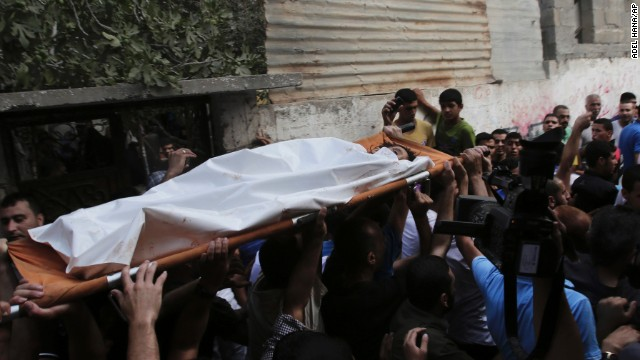 Palestinians carry the body of Gamal Ielian, 10, who was killed in an explosion at a park at the Shati refugee camp, in the northern Gaza Strip, Monday, July 28, 2014. Israeli and Palestinian authorities traded blame over the attack and fighting in the Gaza war raged on despite a major Muslim holiday.