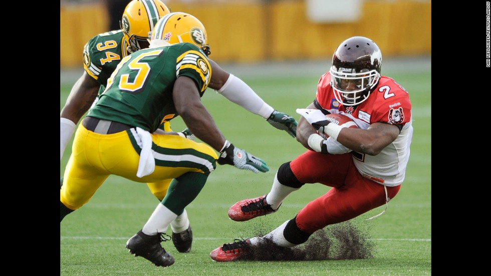Jock Sanders of the Calgary Stampeders makes a cut to avoid Edmonton Eskimos Cameron Sheffield, left, and Gregory Alexandre during a Canadian Football League game in Edmonton on Thursday, July 24. Calgary won 26-22 to improve to 4-0 on the season.