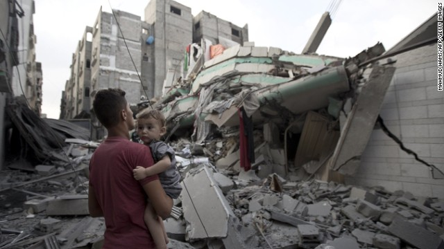 A Palestinian man carrying a child looks at the destroyed house of  Ismail Haniya, Hamas' leader in Gaza, after it was hit by an overnight Israeli air strike, on July 29, 2014 in Gaza City.