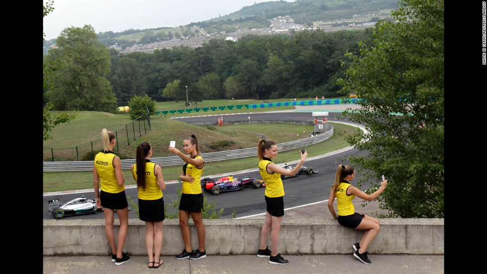Hostesses with the Italian tire company Pirelli take selfies Sunday, July 27, as Formula One drivers compete in the Hungarian Grand Prix near Budapest, Hungary.