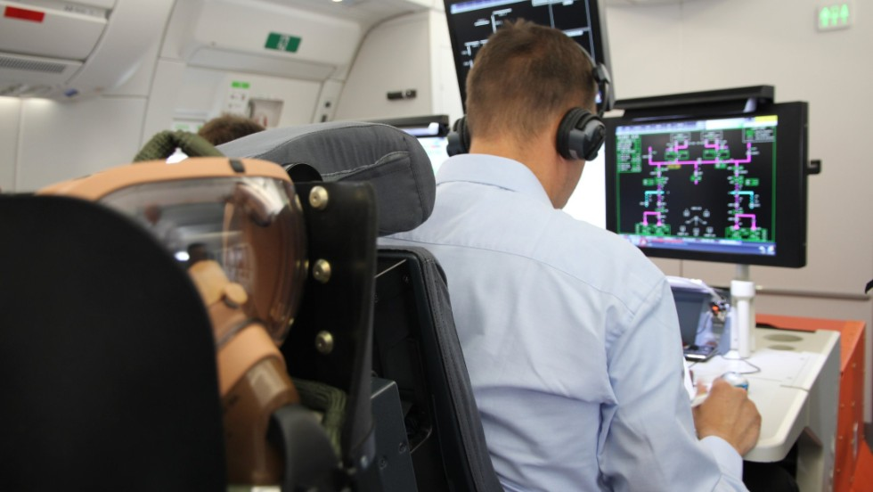 Two engineers man the test station set up in the rear cabin of the plane.
