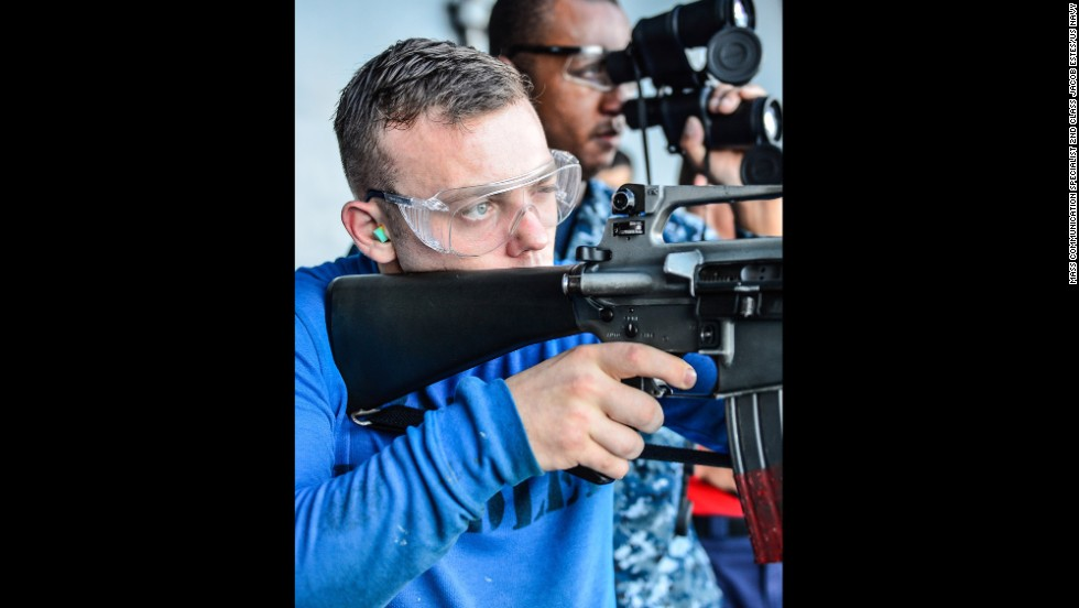 Airman Arthur Bowlby peers through his sight during an M16 rifle qualification aboard the aircraft carrier USS Ronald Reagan on July 18.