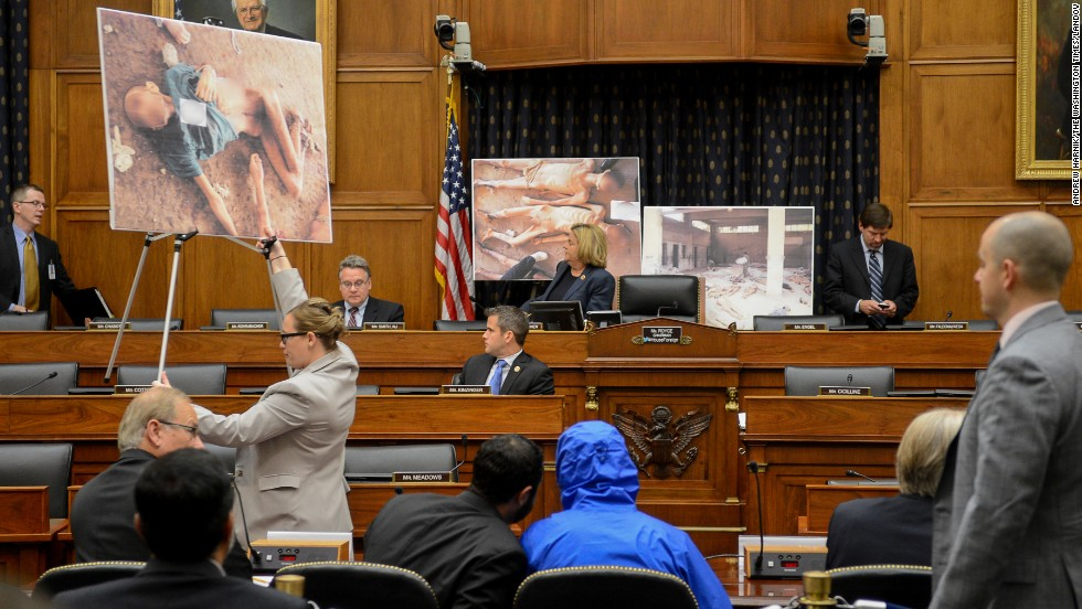 "Photographs of victims of the Bashar al-Assad regime are displayed as a Syrian Army defector known as ""Caesar,"" center, appears in disguise to speak before the House Foreign Affairs Committee in Washington. The briefing on Thursday, July 31, was called ""Assad's Killing Machine Exposed: Implications for U.S. Policy."" Caesar was apparently a witness to al-Assad's brutality and has <a href=""http://www.cnn.com/2014/08/04/world/meast/syria-crisis-remember/index.html"">smuggled more than 50,000 photographs</a> depicting the torture and execution of more than 10,000 dissidents."
