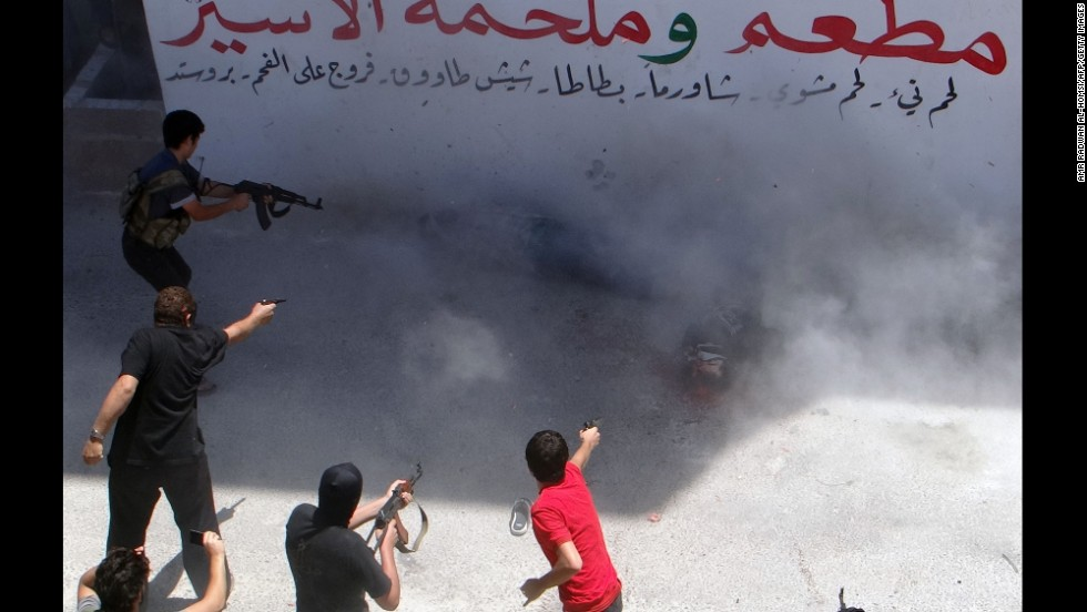 Rebel fighters execute two men Friday, July 25, in Binnish, Syria. The men reportedly were charged by an Islamic religious court with detonating several car bombs.
