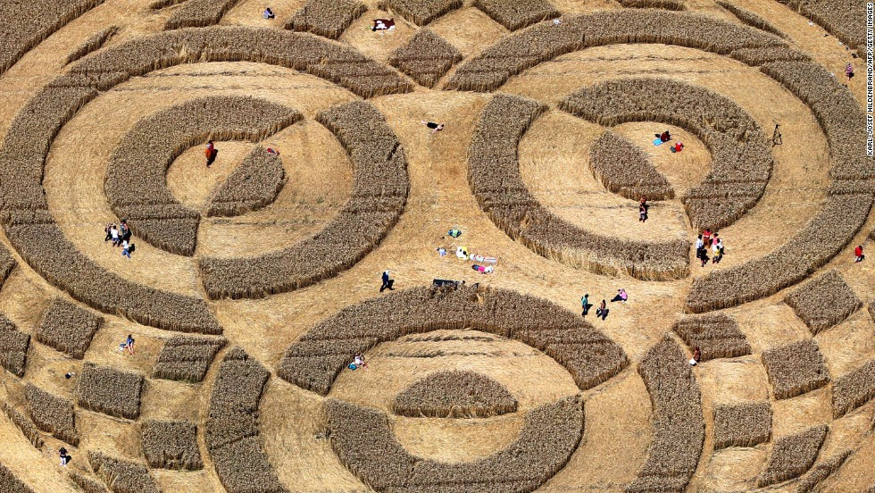 People walk through crop circles at cornfield near Raisting, Germany, on Monday, July 28.
