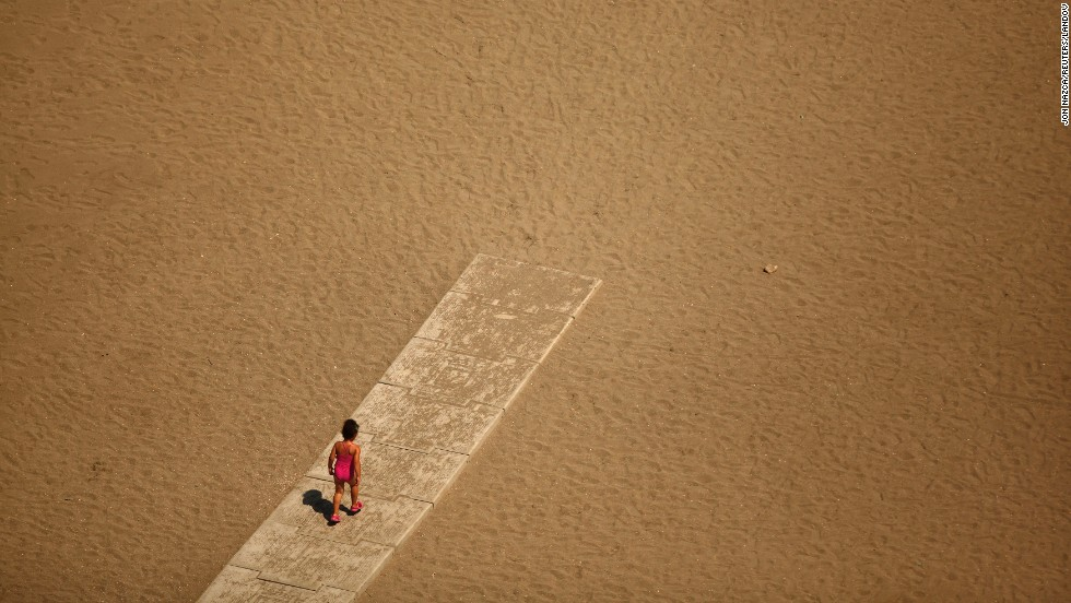 A child walks toward the shore of the Mediterranean Sea at Malagueta Beach in Malaga, Spain, on Sunday, July 27.