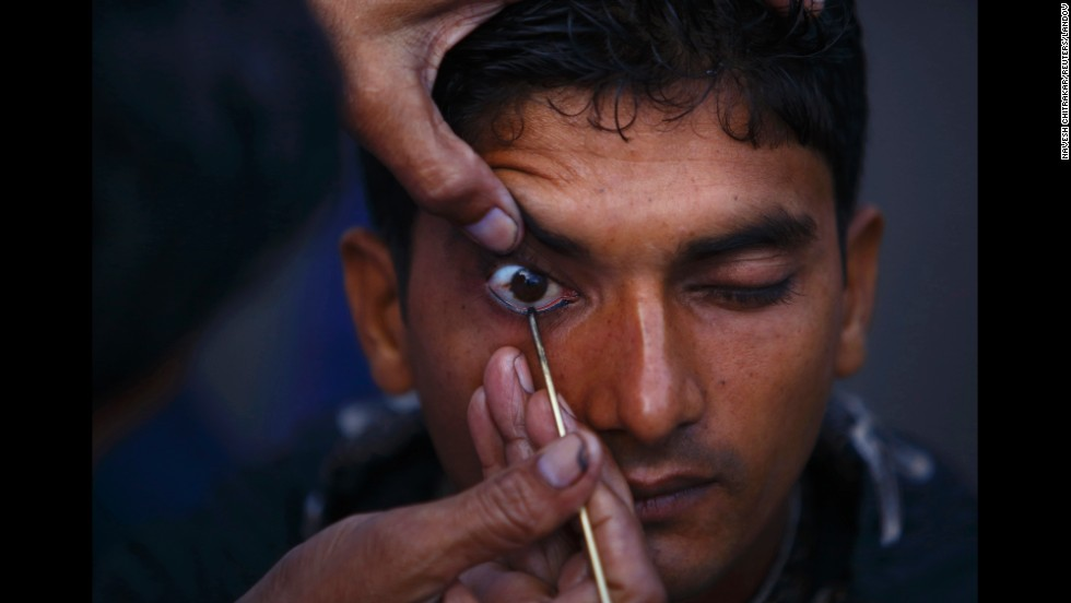 "A Muslim man has kohl applied to his eyelid at a mosque as he arrives for <a href=""http://religion.blogs.cnn.com/2014/06/28/the-belief-blog-guide-to-ramadan/"">Eid al-Ftir</a> mass prayers, in Kathmandu, Nepal, on Tuesday, July 29."
