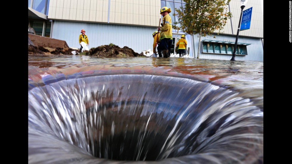 "Firefighters work near an open drain on the UCLA campus, <a href=""http://www.cnn.com/2014/07/30/us/california-ucla-water-main-break/index.html?iref=storysearch"" target=""_blank"">which was flooded by a broken water main</a> in Los Angeles on Tuesday, July 29."