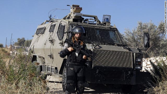 A female Israeli soldier stands next to an armoured vehicle during clashes with Palestinian protesters following a demonstration in the West Bank village of Bilin, on July 31, 2014, in support of Palestinians from the Gaza Strip. Israel vowed it would not pull troops out of Gaza until they finish destroying a network of cross-border tunnels, despite sharp United Nations criticism over the Palestinian death toll. AFP PHOTO/ABBAS MOMANI (Photo credit should read ABBAS MOMANI/AFP/Getty Images)