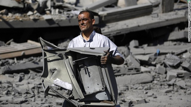 A Palestinian men gathers his belongings from the rubble of his home in Jabalia in the northern Gaza Strip on August 1, 2014.