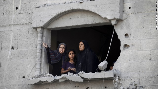 Palestinians look at the wreckage from a damaged window following an Israeli strike, in Rafah, in the southern Gaza Strip on August 2, 2014.