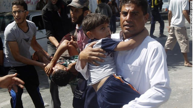 Palestinians carry injured people following an Israeli military strike on a UN school in Rafah, in the southern Gaza Strip on August 3, 2014.