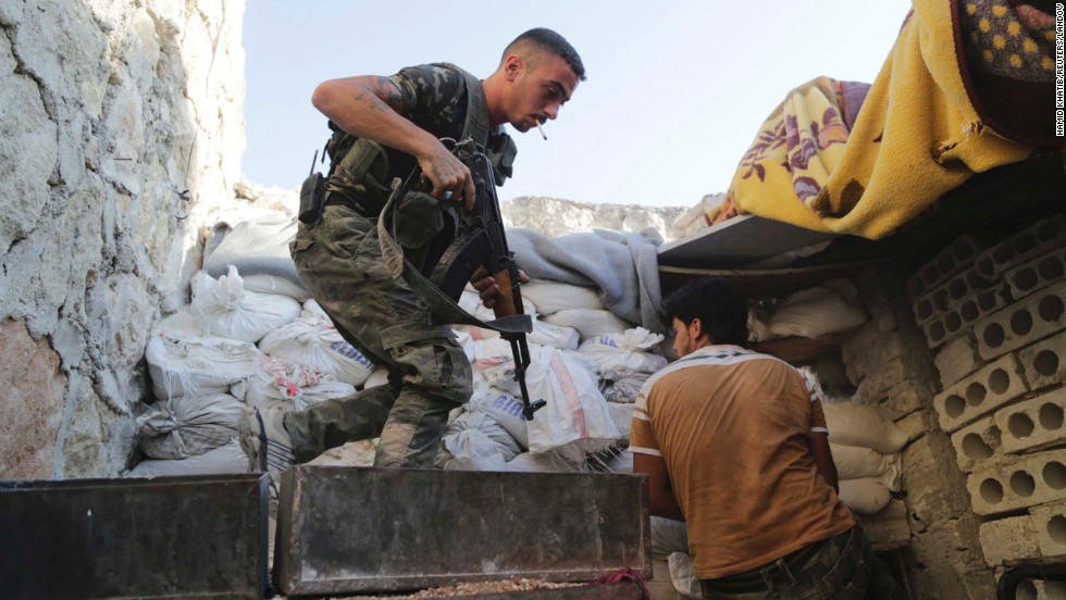 Syrian rebel fighters take up positions behind sandbags in Aleppo on Wednesday, July 30.