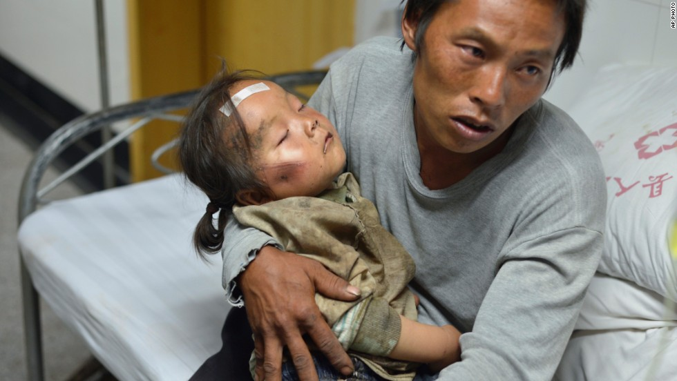 A man holds an injured child at a hospital in China's Ludian County on August 4.