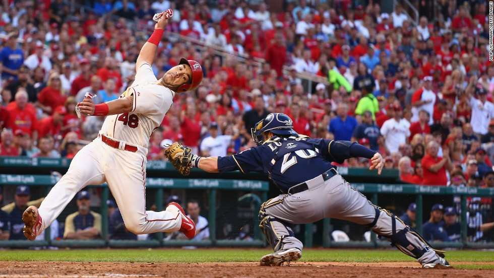 Tony Cruz of the St. Louis Cardinals avoids a tag from Milwaukee catcher Jonathan Lucroy and scores a run Saturday, August 2, in St. Louis.