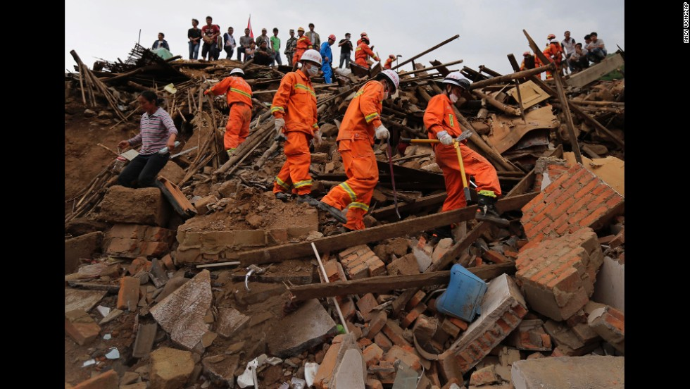 Rescue workers walk over rubble in Longtoushan on August 5.