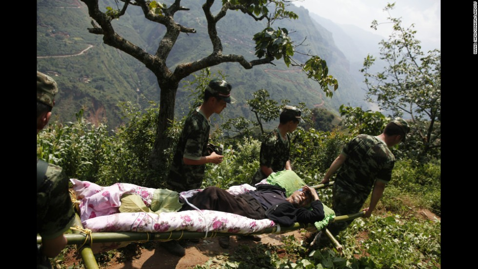Rescue workers carry an injured man in the village of Hongshiyan, China, on August 5.