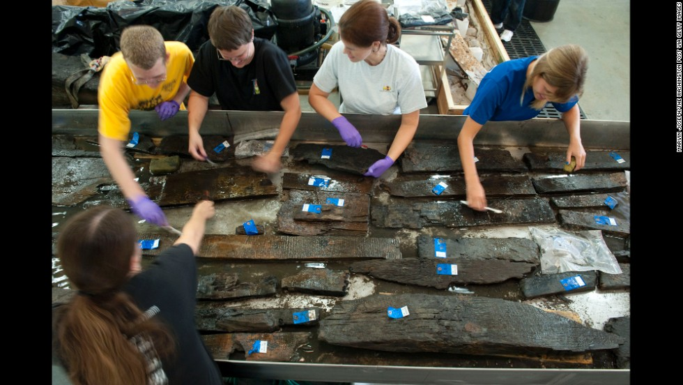 Volunteers and curators from the Maryland Archeological Conservation Laboratory clean timbers from the ship in August 2010. For more than 200 years, the ship was beneath New York City's World Trade Center.