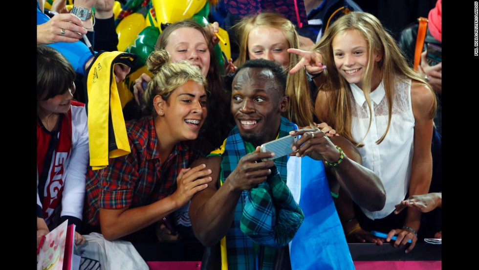 Jamaican sprinter Usain Bolt takes a selfie with fans after he and his team won the 4x100-meter relay Saturday, August 2, at the Commonwealth Games in Glasgow, Scotland.