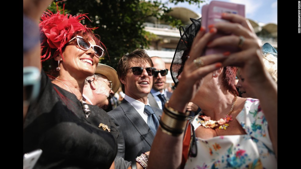A group of women takes selfies with actor Tom Cruise on Thursday, July 31 -- Ladies Day at the Goodwood horse races in Chichester, England.