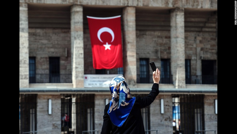 A woman takes a selfie in front of the Olympic Stadium in Berlin, which had a Turkish flag on it Sunday, August 3. For the first time, Turkish nationals in Germany were able to cast a vote in the Turkish presidential elections.