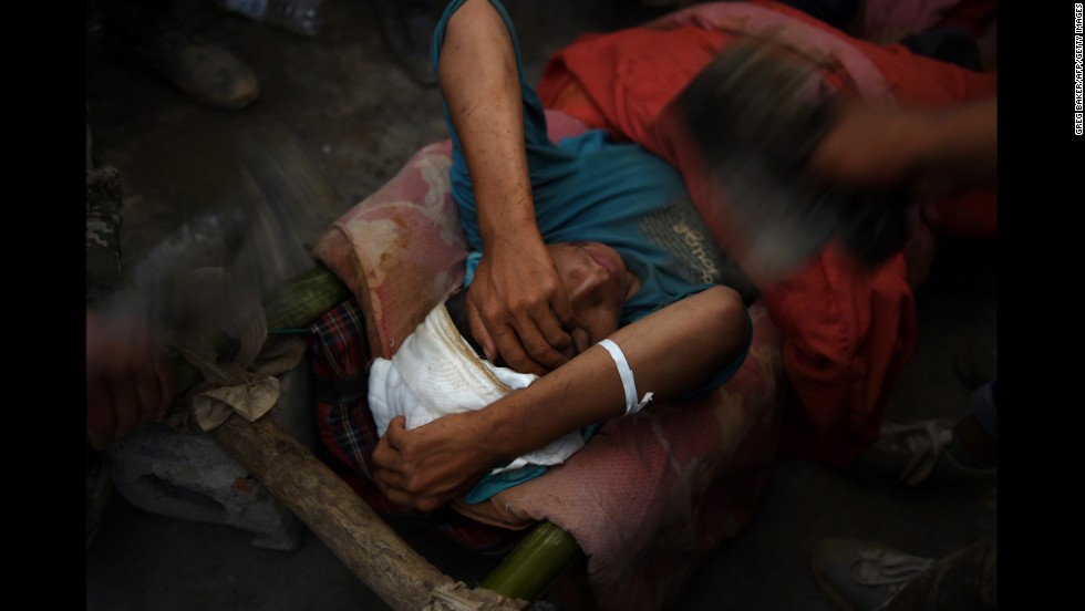 An injured earthquake survivor is fanned while waiting in the corridor of a school before being transferred to an ambulance in Longtoushan on August 6.