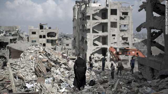 A Palestinian woman walks through the rubble of destroyed buildings in part of Gaza City's al-Tufah neighbourhood as the fragile ceasefire in Gaza entered a second day on August 6, 2014.