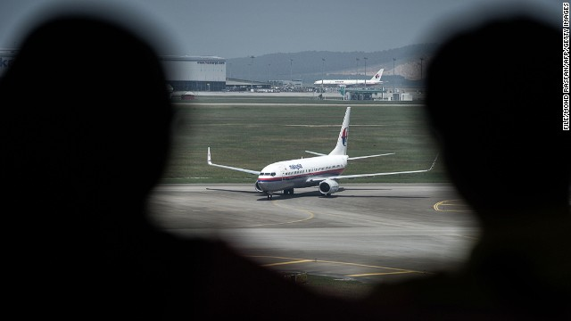 File photo: People look at a Malaysia Airlines plane on the tarmac at Kuala Lumpur International Airport in Sepang on July 21, 2014.