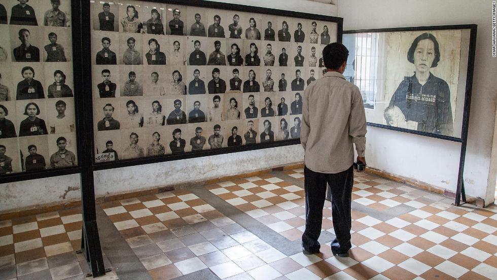 A Cambodian man stands by a wall of photographs of prisoners of the Khmer Rouge regime in one of the rooms of Tuol Sleng prison, also known as S-21, on August 6 in Phnom Penh.