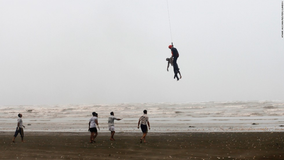 A Pakistan Navy diver, attached to a rope from a helicopter, holds a dead body that was recovered during a search-and-rescue operation Friday, August 1, at Clifton Beach in Karachi, Pakistan. A day earlier, rescuers had recovered the bodies of more than two dozen men who had ventured into the rough Arabian Sea during the Eid holidays.