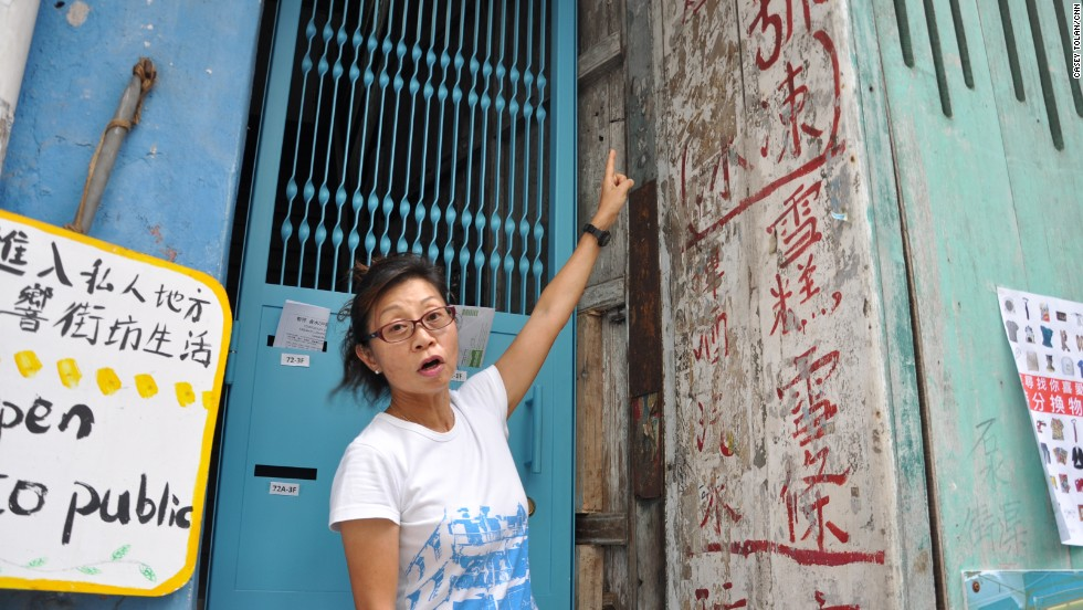 Maria Kwok, a volunteer tour guide who has lived in the neighborhood for almost 30 years, points out old Chinese characters on a wall of the Blue House.
