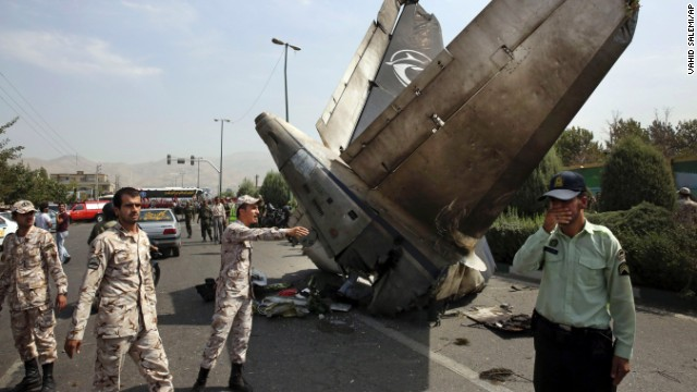 Iranian Revolutionary Guards and police officers inspect the site of a passenger plane crash in Tehran, Iran's capital.