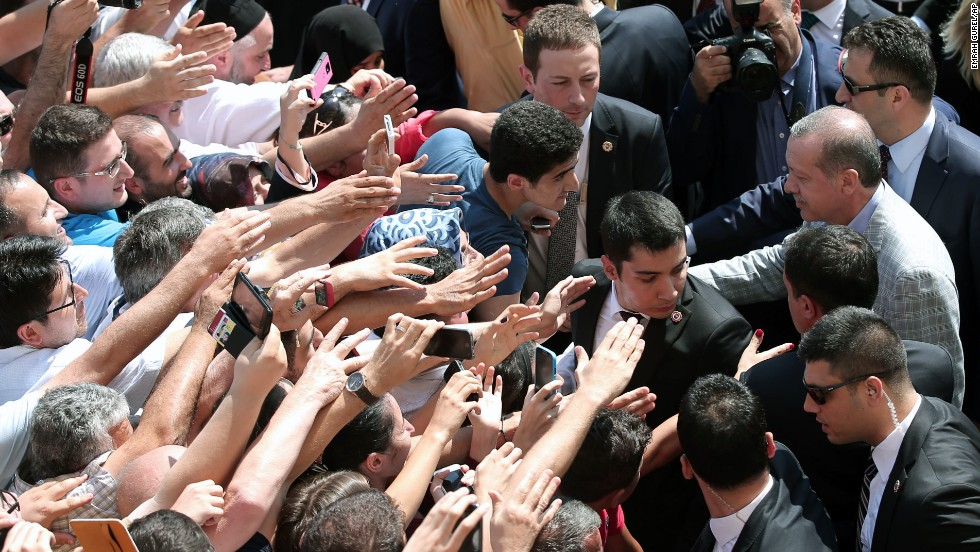 Erdogan shakes hands with cheering supporters outside an Istanbul polling station on August 10.
