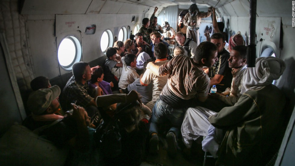 Yazidi people sit on the aircraft with members of the CNN crew.