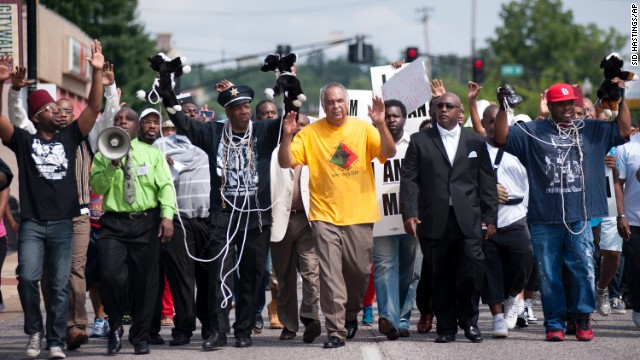Protesters fill Florissant Road in downtown Ferguson, Mo. Monday, Aug. 11, 2014, marching along the closed street. The rally marched along the street in front of the town's police headquarters to protest the shooting of 18-year-old Michael Brown by Ferguson police officers on Saturday. (AP Photo/)