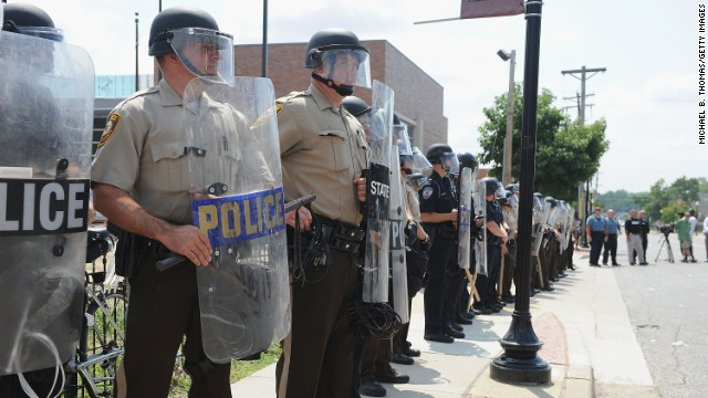 St. Louis County Law Enforcement Officers stand in riot gear during a protest of the shooting death of 18-year-old Michael Brown by a Ferguson police officer, outside Ferguson Police Department Headquarters August 11, 2014 in Ferguson, Missouri.  Civil unrest broke out as a result of the shooting of the unarmed black man as crowds looted and burned stores, vandalized vehicles and taunted police officers. Dozens were arrested for various infractions including assault, burglary and theft.  (Photo by )