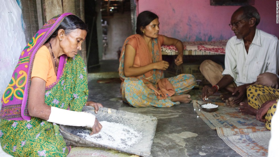 Sadhana, pictured with her parents at home in Dongri village in western India, is one of five daughters and is the main breadwinnner in the family.