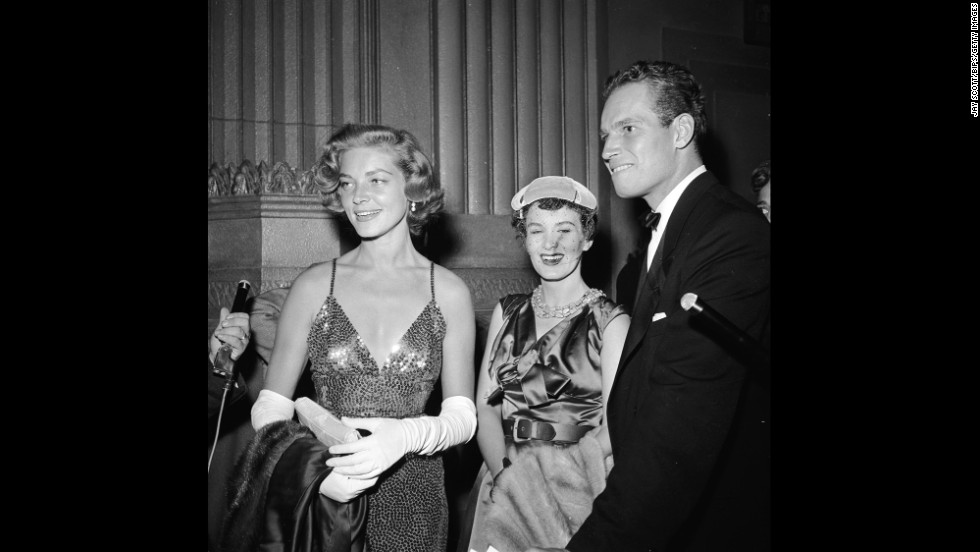 "In 1954, Bacall and actor Charlton Heston attend the film premiere of ""A Star Is Born."""