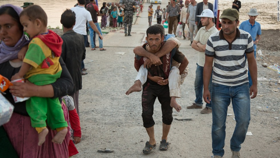 A young refugee carries a disabled man across the bridge.