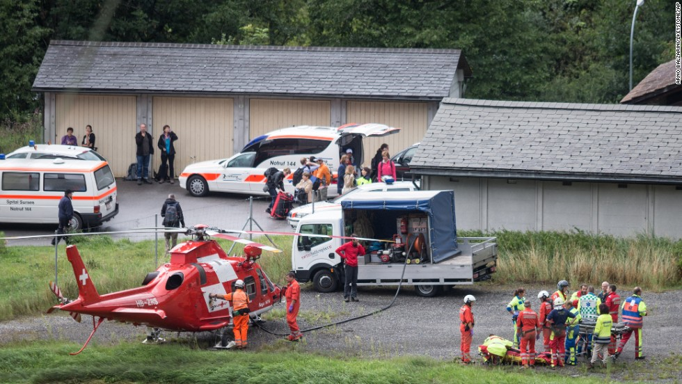 At right, rescue forces recover a victim of the derailment.