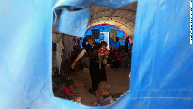 A woman and children take shelter inside a tent at the Bajid Kandala camp on August 13.