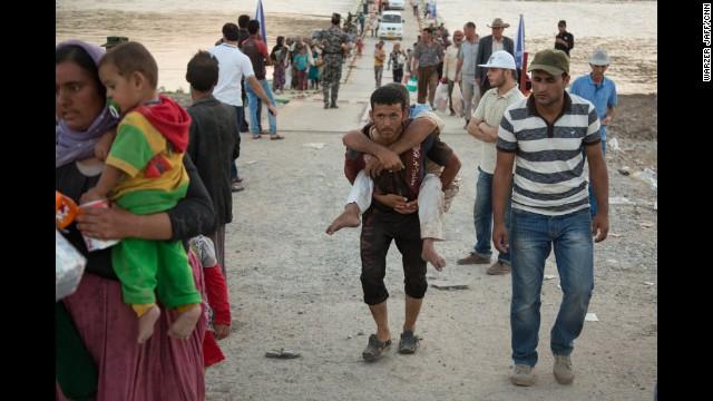 ZHAKO, IRAQ:  A young man carries a handicapped Yazidi across the Pesh Khabor bridge.  Thousands of Iraqi refugees streamed across a bridge into Iraqi Kurdistan, fleeing ISIS militants.  Photo by Warzer Jaff for CNN, August 12.  Watch CNN's Ivan Watson's report at   CNN.COM.