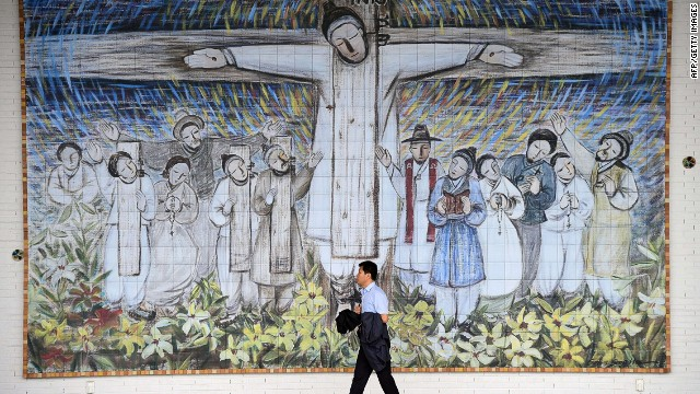 This picture taken on August 7, 2014 shows a man passing in front of a huge wall painting for Korea's Catholic martyrs at Solmoe Shrine in Dangjin, 85 kms southwest of Seoul. Pope Francis will pay tribute to the courage and sacrifice of South Korea's first Catholics when he beatifies 124 tortured and executed martyrs at a special mass in Seoul on August 16. AFP PHOTO / JUNG YEON-JEJUNG YEON-JE/AFP/Getty Images