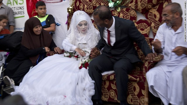 Omar Abu Namar, 30, (R) and his wife Heba Fayad, 23, (L) attend their wedding ceremony at a UN school school in Gaza City's Shati refugee camp on August 13, 2014.