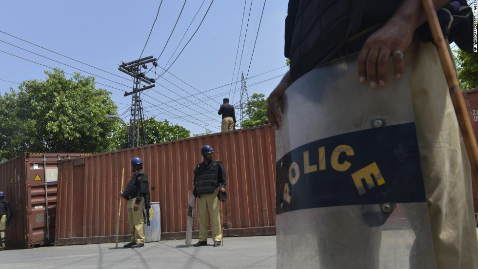 Pakistani policemen stand alongside a roadblock of shipping containers near the Lahore home of cleric Tahir ul Qadri on August 13 as the country prepares for a massive anti-government march.