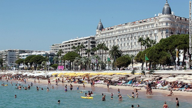 People frolic in the water at a beach in Cannes in August 2012.