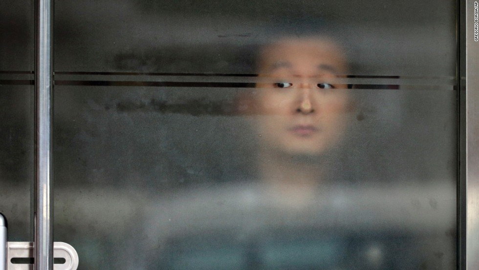 "A security guard peers out of a glass door while Pope Francis and South Korean President Park Geun-hye meet at the presidential house in Seoul, South Korea, on Thursday, August 14. The Pope's <a href=""http://www.cnn.com/2014/08/13/asia/gallery/pope-francis-south-korea/index.html"">trip to South Korea</a> marks the first papal visit to the country since Pope John Paul II visited 25 years ago."