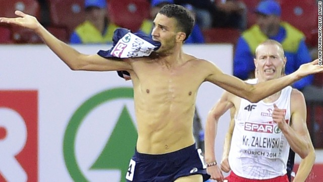 French athlete Mahiedine Mekhissi-Benabbad strips off his running vest in the home straight of the 3,000m steeplechase.