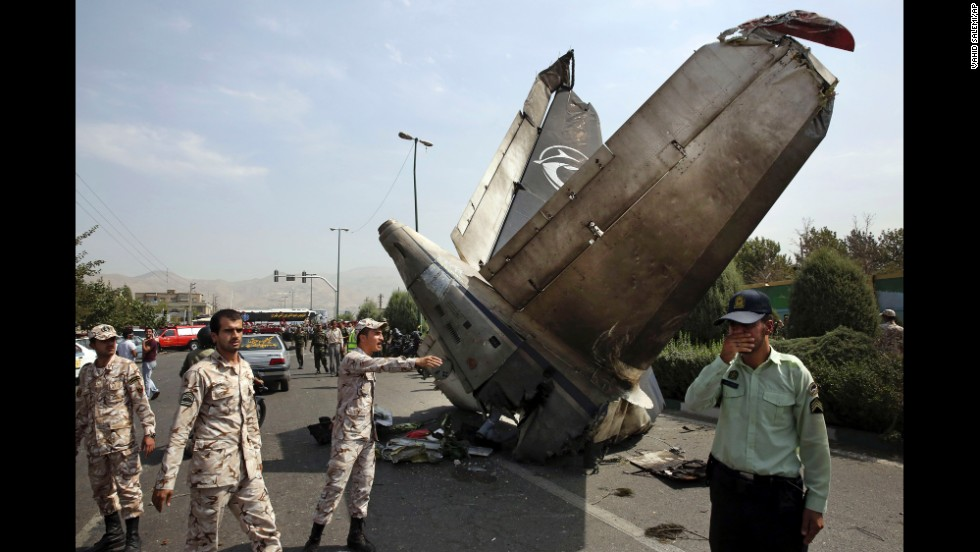 "Iranian Revolutionary Guards and police officers inspect the site of a <a href=""http://www.cnn.com/2014/08/10/world/meast/iran-plane-crash/index.html"">passenger plane crash</a> in Tehran, Iran, on Sunday, August 10. Sepahan Airlines Flight 5915 was carrying 40 passengers and a crew of eight when it went down shortly after takeoff, according to official news agencies in Iran."